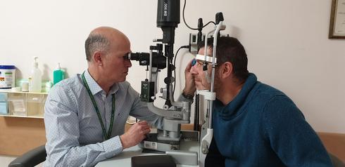"""ד""""ר ערן פרס (משמאל)  וולרי בבדיקת עיניים"""