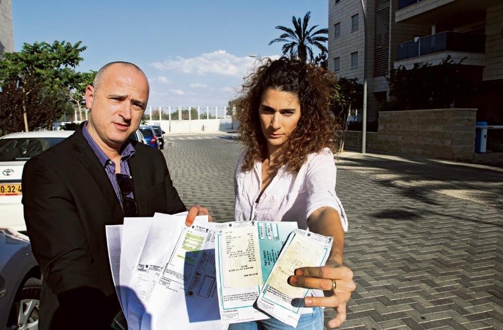 """הדס אלמליח ועו""""ד אריאל טרון עם דוחות החנייה   צילום: אבי מועלם"""